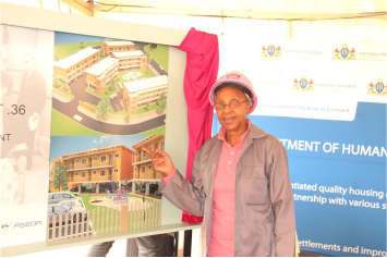 Member of South Africa Women In Construction (SAWIC) (Gauteng Province) Ms Thami Siwisi from Zenande Primary Cooperative next to the plan that the Human Settlement Department and partners project that will take 3 years to complete.